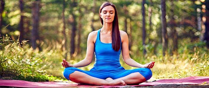 Eine junge Frau macht Yoga in der Natur