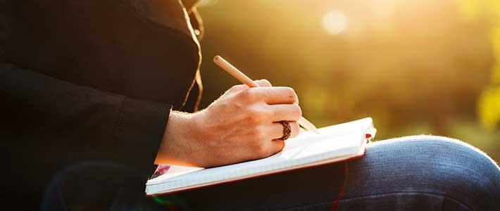 Frau schreibt etwas in ihr Notizbuch
